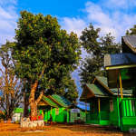 Green wooden cottages at Bara Pathing Eco Hut